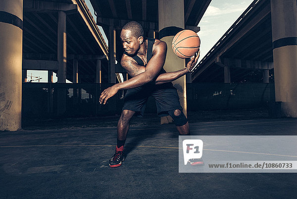 Young man bending forward balancing basketball on hand  looking away