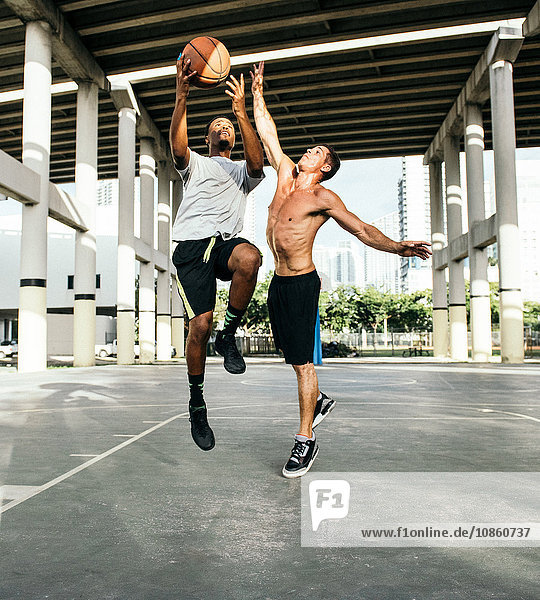 Men on basketball court jumping for basketball