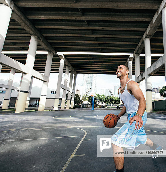 Young man on basketball court holding basketball looking up smiling