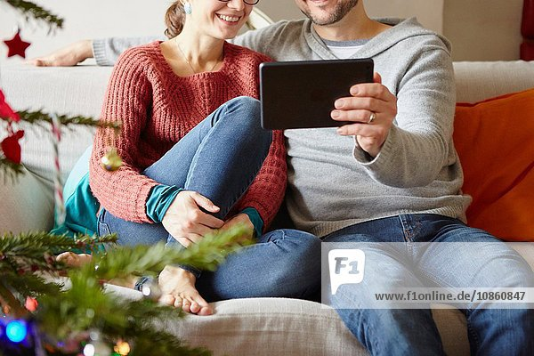 Adult couple sitting on sofa reading digital tablet at xmas