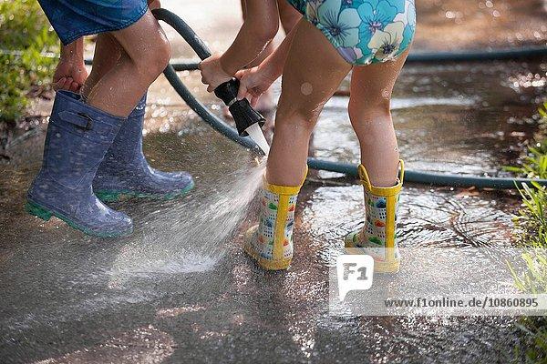 Kinder spielen mit Wasserschlauch auf dem Bürgersteig