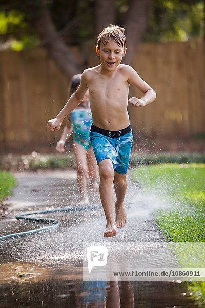 Children running in water on sidewalk