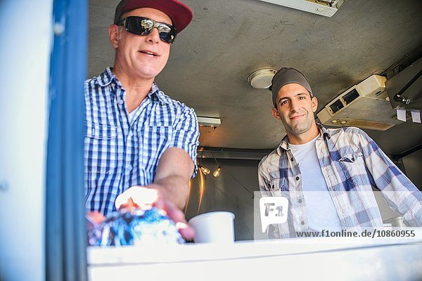 Low angle view of men in catering van looking through hatch at camera smiling