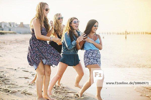 Frauen mit Sonnenbrille am Strand  die lachend herumalbern
