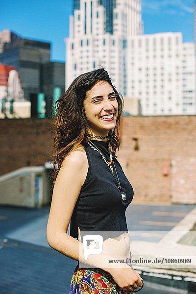 Seitenansicht einer Frau mit Nasenring auf dem Dach  die ein Kropf-Oberteil trägt und mit geschlossenen Augen in die Kamera schaut  lächelnd  Boston  Massachusetts  USA