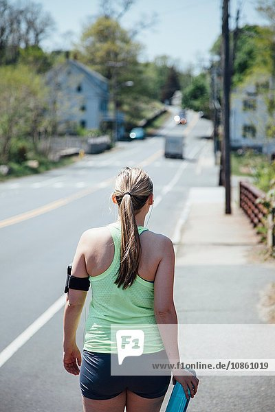 Rear view of woman wearing activity tracker carrying water bottle walking along road