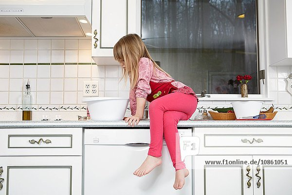 Girl looking into mixing bowl whilst sitting on kitchen counter