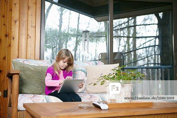 Mädchen sitzt auf Wohnzimmer-Sofa und benutzt Touchscreen auf digitalem Tablet
