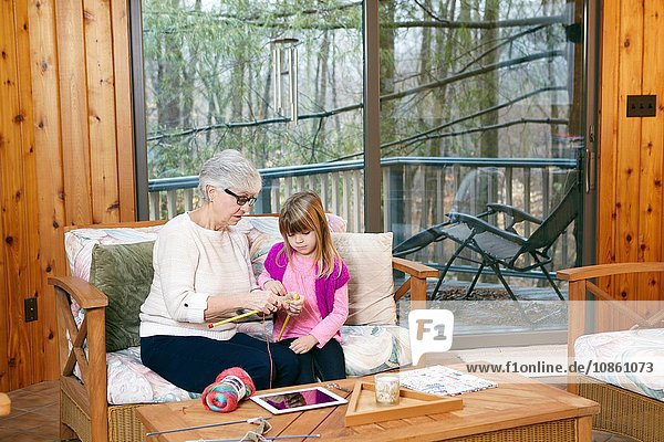 Senior woman teaching granddaughter how to knit on living room sofa