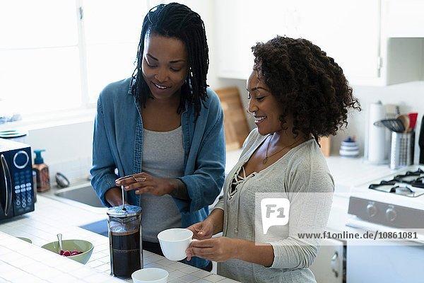 Two female friends  in kitchen  making coffee