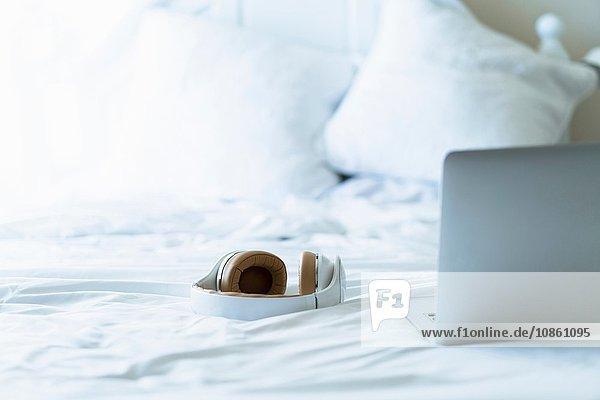 Laptop und Kopfhörer auf dem Bett  Stilleben