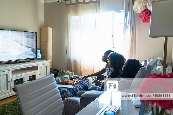 Three female friends relaxing at home  watching TV