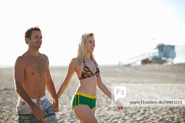 Couple walking on beach holding hands smiling