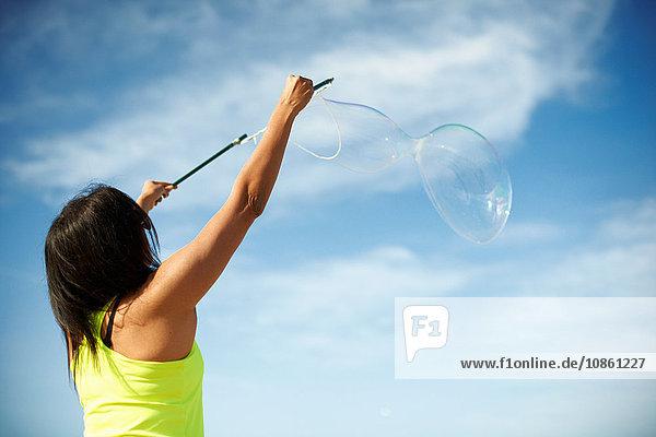 Rückansicht der Frau  die Arme mit Hilfe von Blasenstäben zum Blasenmachen erhoben