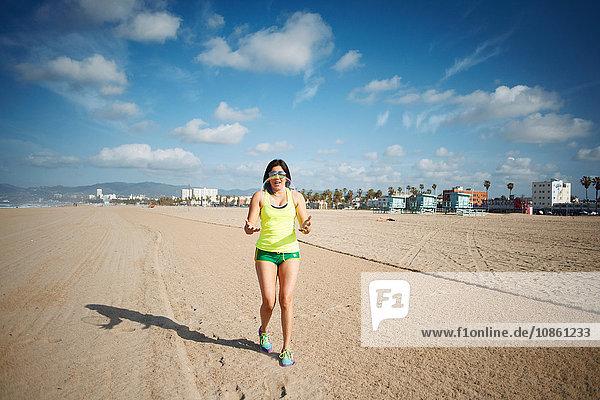 Frontansicht einer Frau am Strand in voller Länge  die eine Blase fängt