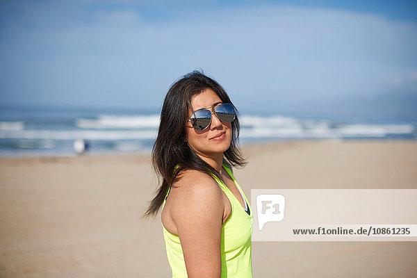 Frau mit Sonnenbrille am Strand  die in die Kamera schaut