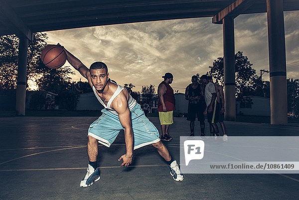 Man on basketball court bending forward holding basketball