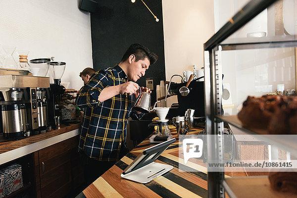 Kellner  die an der Kaffeetheke Wasser in den Kaffeefilter gießen