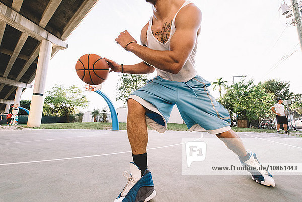 Cropped view of man on basketball court running  bouncing basketball