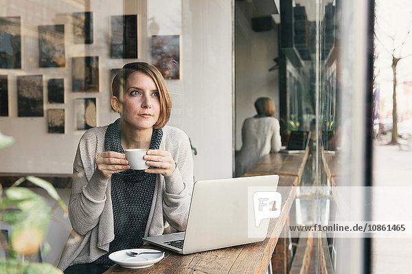Frau trinkt Kaffee  während sie vom Fensterplatz des Kaffeehauses blickt