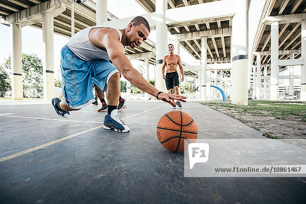Men on basketball court reaching for basketball