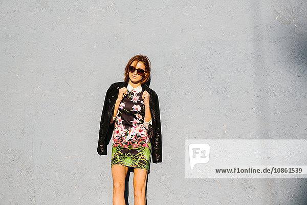 Porträt einer jungen Frau  in Kleid und Lederjacke  im Freien