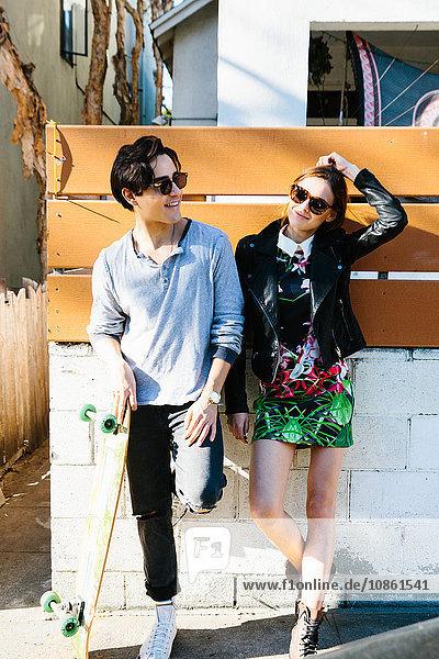 Junges Paar steht zusammen im Freien,  junger Mann hält Skateboard