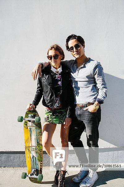 Porträt eines jungen Paares im Freien  Frau hält Skateboard