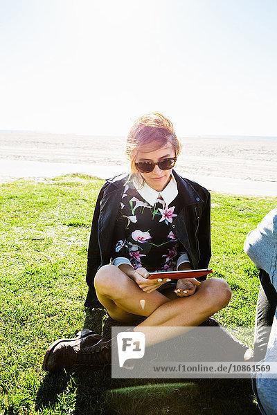 Junge Frau sitzt im Schneidersitz auf Gras und schaut auf ein digitales Tablet