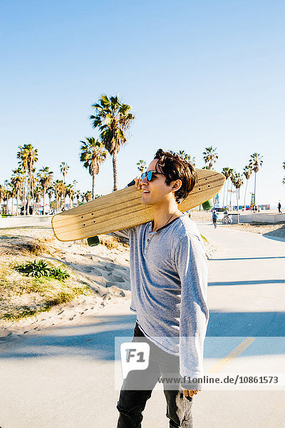 Young man walking outdoors  carrying skateboard on shoulder