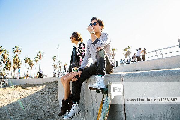 Junges Paar sitzt an der Wand  Mann ruht mit dem Fuß auf dem Skateboard