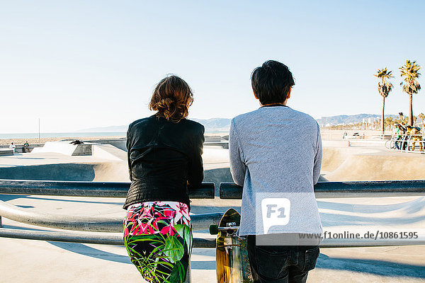 Junges Paar  zusammen stehend  an Geländer gelehnt  Rückansicht