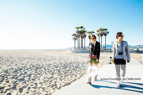 Junges Paar geht am Strandweg entlang