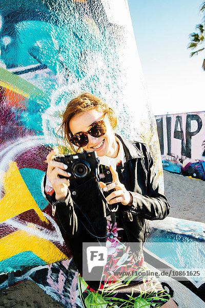 Junge Frau mit Digitalkamera  lächelnd