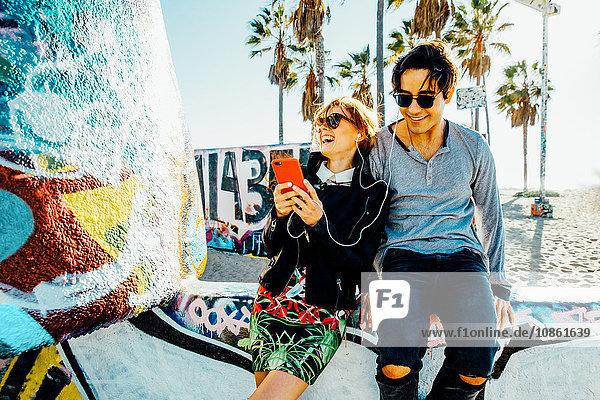 Junges Paar sitzt an der Wand  teilt Kopfhörer und lacht