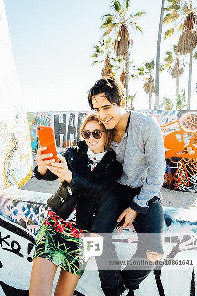 Junges Paar sitzt an der Wand und macht ein Selbstporträt mit einem Smartphone