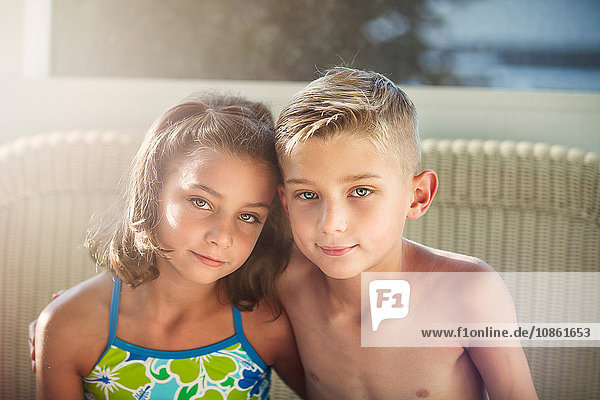 Portrait of boy and girl arms around each other looking at camera smiling