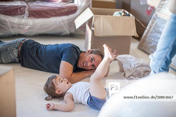 Umzug: Vater und Tochter entspannen sich auf dem Boden des neuen Hauses