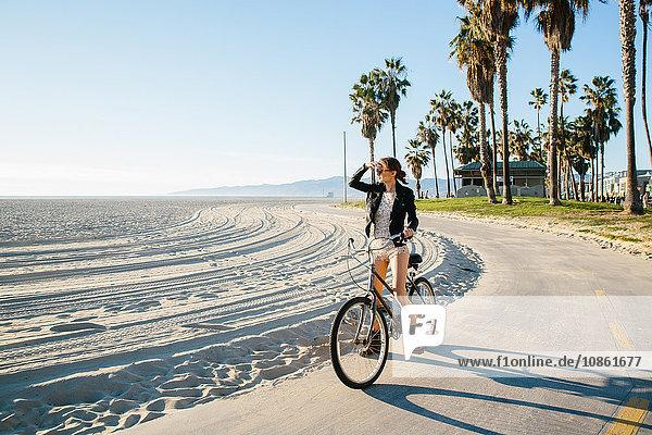 Junge Frau radelt am Strand mit Blick aufs Meer  Venice Beach  Kalifornien  USA