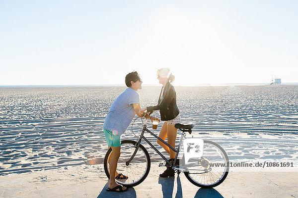 Junges Paar mit Fahrrad beim Plaudern am sonnigen Strand  Venice Beach  Kalifornien  USA