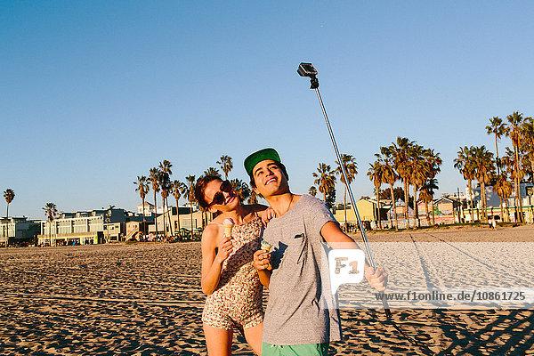 Junges Paar beim Selbstfahren mit Smartphone-Stick am Strand  Venice Beach  Kalifornien  USA
