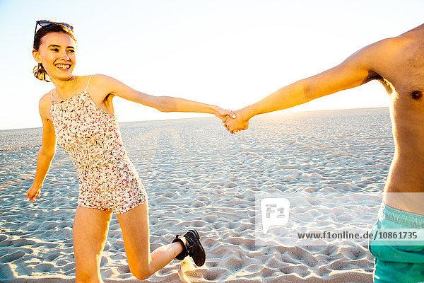 Junges Paar in Badeanzug und Shorts hält am Strand Händchen  Venice Beach  Kalifornien  USA