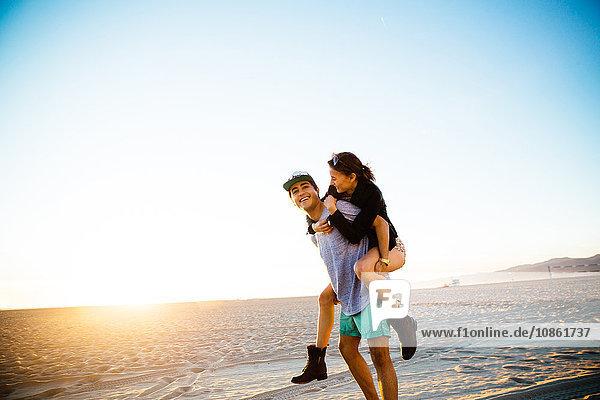 Junger Mann schenkt seiner Freundin ein Huckepack am Strand  Venice Beach  Kalifornien  USA