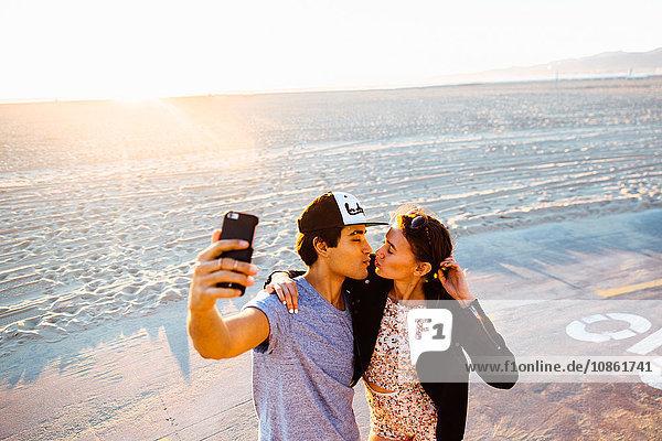 Junges Pärchen  das sich für Smartphone-Selfie am Strand zusammenrauft  Venice Beach  Kalifornien  USA