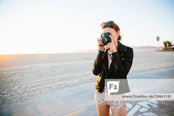 Young woman photographing with instant camera on beach  Venice Beach  California  USA