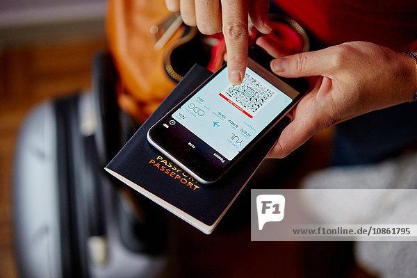 Frau mit Reisepass und Smartphone  Smartphone mit QR-Code  Draufsicht