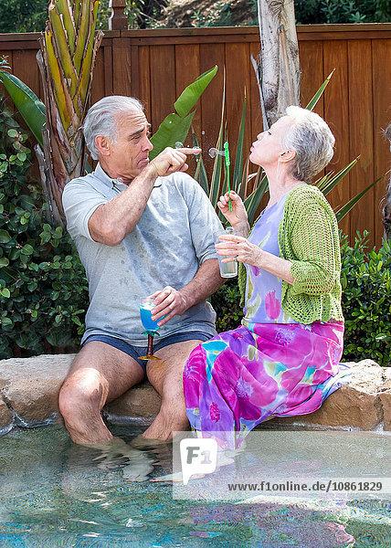 Älteres Paar bläst Blasen am Pool
