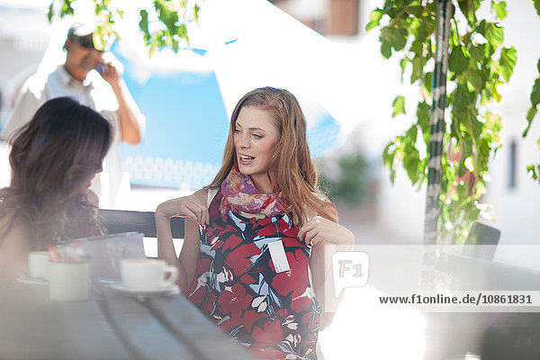 Weibliche Shopping-Freundinnen zeigen neue Kleider im Straßencafé in der Stadt