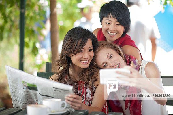 Drei Freundinnen posieren für Smartphone-Selfie im Bürgersteig-Café in der Stadt