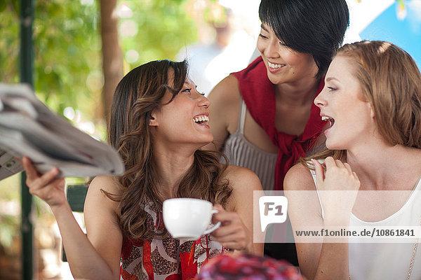 Drei Freundinnen lachen zusammen in einem Straßencafé in der Stadt